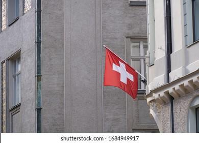 Schweizer Flagge hängt von der Gebäudefassade.