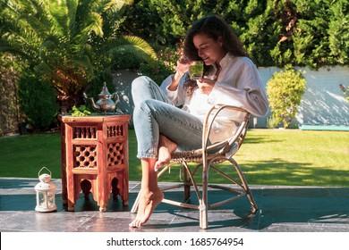Mujer marroquí bebiendo té árabe tradicional en casa. Cultura y tradiciones árabes. Estilo de vida musulmán. Mujer joven árabe con rasgos étnicos que huele té árabe de menta en su jardín.