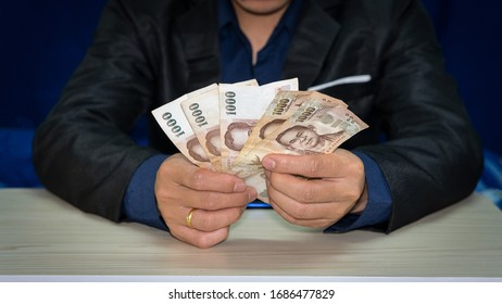 A thousand bank notes in the hands of a man in a black suit, amount 5,000.