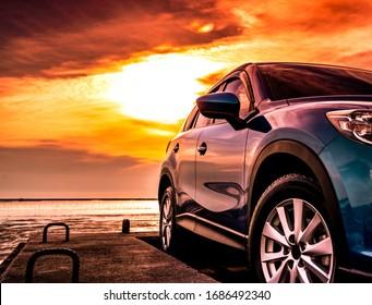Blauwe luxe Suv-auto geparkeerd op betonweg door zee strand met mooie rode avondrood. Zomervakantie op tropisch strand. Rondrit. Vooraanzicht sport en modern design SUV-auto. Zomerreizen met de auto.