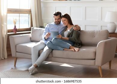 In voller Länge liebevoller junger Mann, der attraktive Frau Freundin umarmt, den digitalen Computer-Tablet-Bildschirm betrachtet und sich auf bequemer Couch entspannt. Liebespaar, das online im Internet-Shop einkauft.
