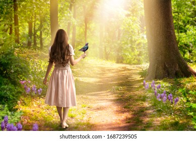 Dama chica con cabello largo vestido con pájaro en mano caminando en el bosque de primavera de cuento de hadas encantado de fantasía con flores y rayos de sol, camino misterioso atraviesa árboles en madera mágica élfica