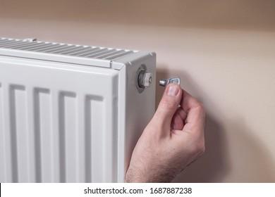 Kühler entlüften. Die Hand des Mannes hält einen speziellen Schlüssel, den er in das Entlüftungsventil einführt.