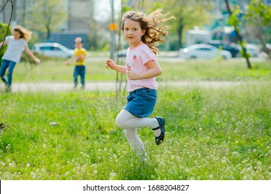 beautiful little girl with developing hair walks in street violating quarantine of coronavirus. girl in pink T-shirt runs across green field. girl plays active games in nature in summer or spring.