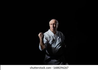 رياضي ذكر عجوز يقوم بتدريب كتلة بيده بمستوى متوسط على خلفية سوداء