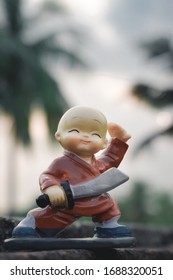 Cute sweet plastic Doll standing with sword and king costume on skateboard dress as wonder prince in action adventure. Close up portrait. Outdoor childhood fun play leisure game toddler background.