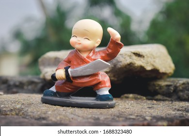 Linda muñeca de plástico dulce de pie con traje de espada y rey en patineta vestido como príncipe maravilla en acción y aventura. Retrato de cerca. Diversión infantil al aire libre, juego de ocio, fondo para niños pequeños.