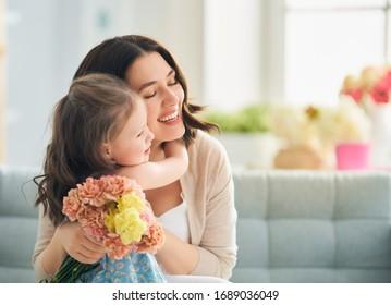 Gelukkige Moederdag! Kinddochter feliciteert moeder en geeft haar bloemen. Moeder en meisje glimlachen en knuffelen. Gezinsvakantie en saamhorigheid.