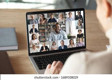 Rückansicht der Mitarbeiterin sprechen Gespräch auf Videoanruf mit verschiedenen gemischtrassigen Kollegen auf Online-Event-Briefing, Arbeitnehmerin haben Webcam-Gruppenkonferenz mit Kollegen auf modernen Laptop zu Hause