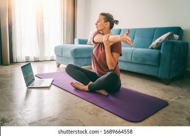 Aantrekkelijke jonge vrouw doet yoga thuis yoga uitrekkende online. Zelfisolatie is nuttig, vermaak en educatie op internet. Gezond levensstijlconcept.