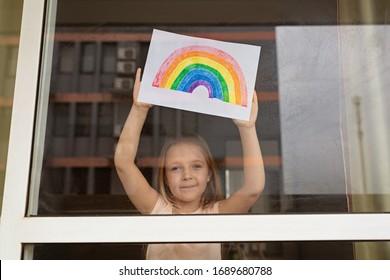Kind schildert regenboog tijdens quarantaine van Covid-19 thuis. Meisje dichtbij venster. Blijf thuis Social-mediacampagne voor coronaviruspreventie, laten we allemaal goed komen, hoop tijdens coronavirus pandemie concept