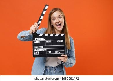 Aufgeregtes junges Frauenmädchen in lässigen Jeanskleidern, die lokal auf orange Wandhintergrund-Studioporträt darstellen. Menschen Lifestyle-Konzept. Kopieren Sie den Speicherplatz. Halten Sie die klassische Filmklappe für schwarze Filme