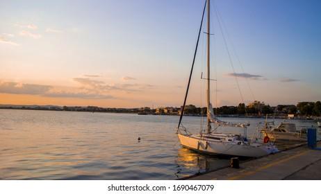 カラフルな夕日でブルガリアの港に横たわるかわいい小さな漁船が完璧なバルカニアの夏休みの思い出を作り出します。ポモリエの黒海/ブルガリア