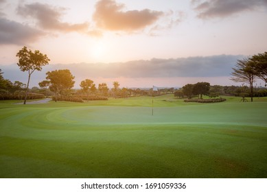 A view landscape green grass at golf course , big trees with black cloud sky background.