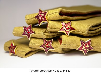 Stack of military caps of the Soviet army with red stars. Garrison cap with a red stars. Red stars with sickle and hammer. Concept for the May 9 Victory Day.