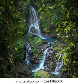 Ustronny tajny naturalny wodospad Pengibul, z sztucznym stosem skały równoważącej na Bali, Indonezja