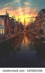 Warmer Sonnenuntergang auf dem Kanal von Amsterdam spiegelte sich auf dem ruhigen Wasser, Niederlande wider
