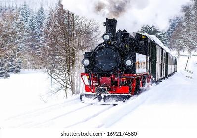 蒸気機関車が雪に覆われた森を駆け抜けます。冬の蒸気機関車の眺め。冬の雪の森で蒸気機関車に乗る