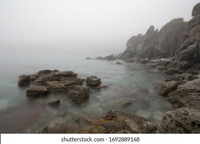 霧の中の岩の多い海岸、水から突き出た石