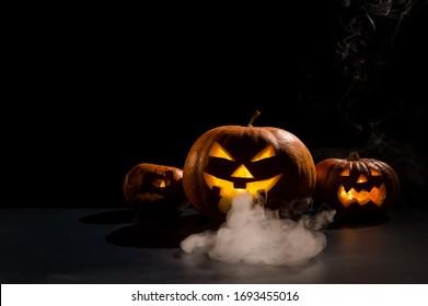 Halloween kaart. jack o lantern met kaarsen gloeien op een zwarte achtergrond. Een rij enge pompoenen met uitgesneden grimassen rookt in het donker.