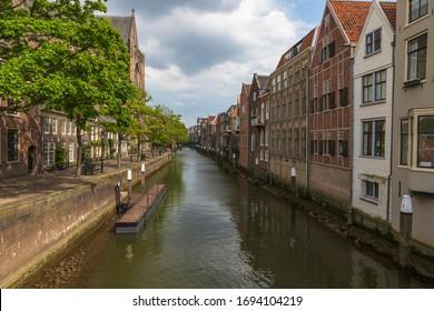 Canal de agua entre casas con camino a lo largo de casas en Dordrecgt en Holanda. El camino está bordeado de árboles.