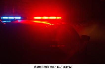 Polizeiauto mit roten und blauen blinkenden Lichtern auf leerem Nachtstraßenhintergrund, Tatort, Nachtpatrouille der Stadt, Kampf gegen Plünderungen während der Quarantäne.