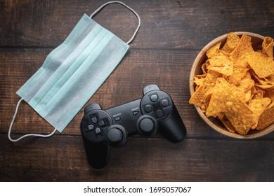 ゲームコンソールrc、ポテトチップスのボウル、木製テーブルの医療用マスク。コロナウイルスコビッド-19検疫外出禁止令。