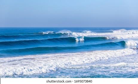 Meeresmeerwellen, die in Richtung Strand rollen und entlang flacher Riffe und Sandbank eine malerische Küstenpanoramalandschaft bremsen.