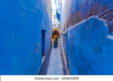 伝統的なインドのインドの女性は、インドのラジャスタン州ジョードプルの青い街の狭い青い通りを歩いているインドのサリーに身を包んだ。
