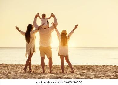 夕日の海のビーチで4人の幸せな家族が腕を上げて立っています
