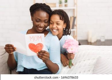 Glückliches Muttertagskonzept. Schwarzes Kind, das ihre Mutter mit Blumen und Karte, copyspace begrüßt