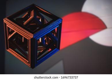 Geometrische Figur aus Holz, Würfel, von verschiedenen Seiten mit unterschiedlichem Licht, Rot und Blau bemalt. Formen im Hintergrund. Weiß. Maße. 3D. Abstrakter Hintergrund für Design. Cyberpunk