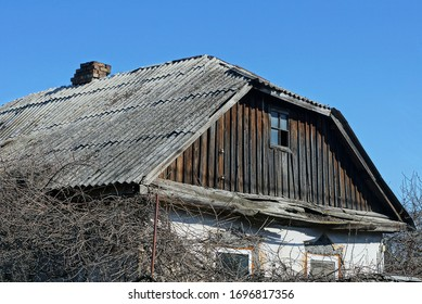 old brown wooden attic of a rural house with a small window under a gray slate roof against a blue sky