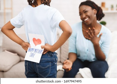Afrikanisches Kind versteckt Grußkarte für Mutter hinter dem Rücken und gratuliert ihr zum Muttertag, selektiver Fokus