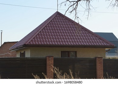 part of a private house under the red tile roof of a brown fence from wooden planks and bricks in the village street on a background of blue sky
