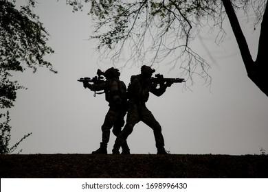 Silhouetten von Armeesoldaten gegen die Sonne, Marinesoldatenteam in Aktion, Feuer und Rauch umzingelt, mit Sturmgewehr und Maschinengewehr geschossen, Feind angegriffen