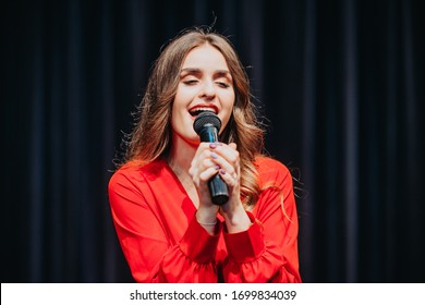 Beautiful woman sings. Attractive young student performs on stage at university. Girl with microphone in hand. Close-up for singer. Fashionably dressed lady at music festival. Actress doing the show