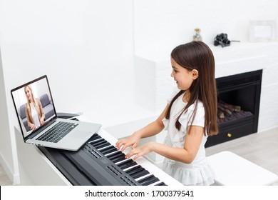 コロナウイルスが蔓延している間、またはcovid-19の危機的状況、vlogまたは教師が生徒に自宅から学ぶことを教えるために、オンラインピアノレッスンを行うオンラインピアノレッスンまたはEクラス学習のシーン。
