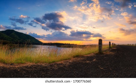 Panoramic landscape  view of sunset or sunrise sky clouds over lake dam mountain and asphalt road. Concept of country side landscape and nature view