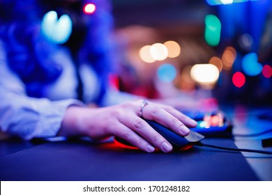 Woman gamer sitting table, playing online games on computer, neon color.