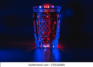 Tincture of red color in a crystal glass in neon lighting