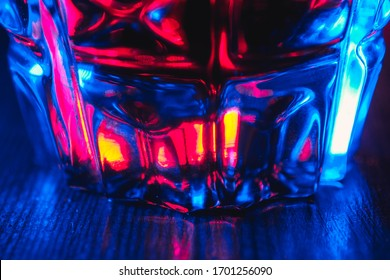 Close up tincture of red color in a crystal glass in neon lighting