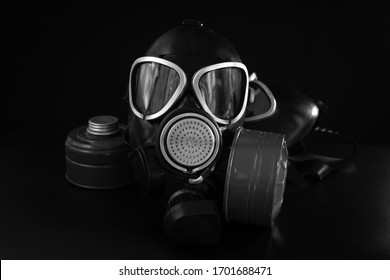 Military gas mask with a filter box on a black background. Personal respiratory protection from dust, toxic substances and viruses. In center of picture. Black and white