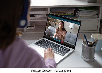School teen girl student wears headphones distance learning with online teacher on computer screen. Web tutor gives remote class teaching teenage pupil elearning from home. Over shoulder close up view