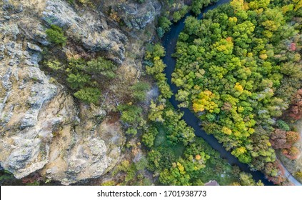 Aerial shot of trees changing to autumn colors with a flowing river in Logan Canyon of northern Utah