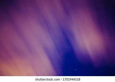 Night sky with stars and blurry and moving clouds with a glare of light from a distant city.
