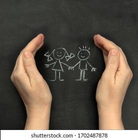 Hände schützen Kinder an der Tafel mit Kreide gezeichnet. Konzept für den Internationalen Kindertag, 1. Juni.