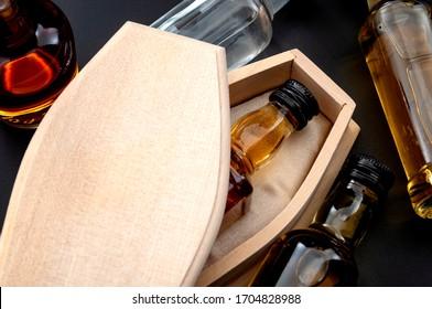 Alkoholmissbrauch tötet, Verzweiflungstodesfälle und Trinkproblemkonzept mit Schnapsflasche im hölzernen Sarg lokalisiert auf dunklem bedrohlichem Hintergrund