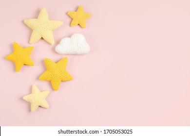 ピンクの背景にニットのおもちゃの黄色い星。ベビー用品やアクセサリー。フラットレイ、上面図