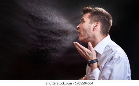 Man is coughing trying to cover his mouth.  Influenza, cold, flu, coronavirus. Infection through an airborne droplet. Droplets of saliva, water and viruses. Cough and sneeze. Man 30-40 aged